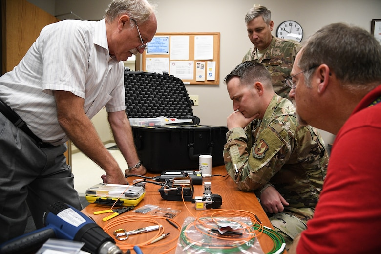 Laurence Wesson, left, trains Tech. Sgt. Kenan Harvey on a fusion splicer for fiber optic cable repair at Hill Air Force Base, Utah, Sept. 10, 2019.