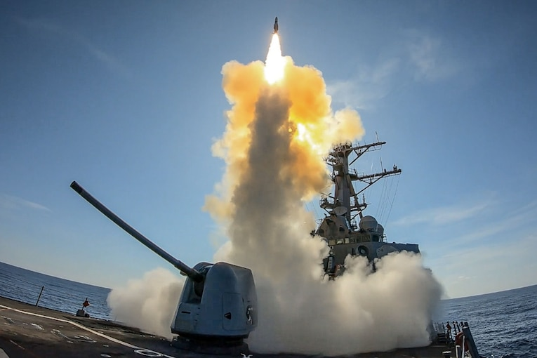 A missile launches from a military ship.