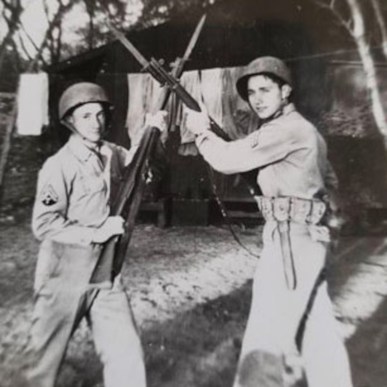 Two soldiers pose for a photo with their rifles crossed