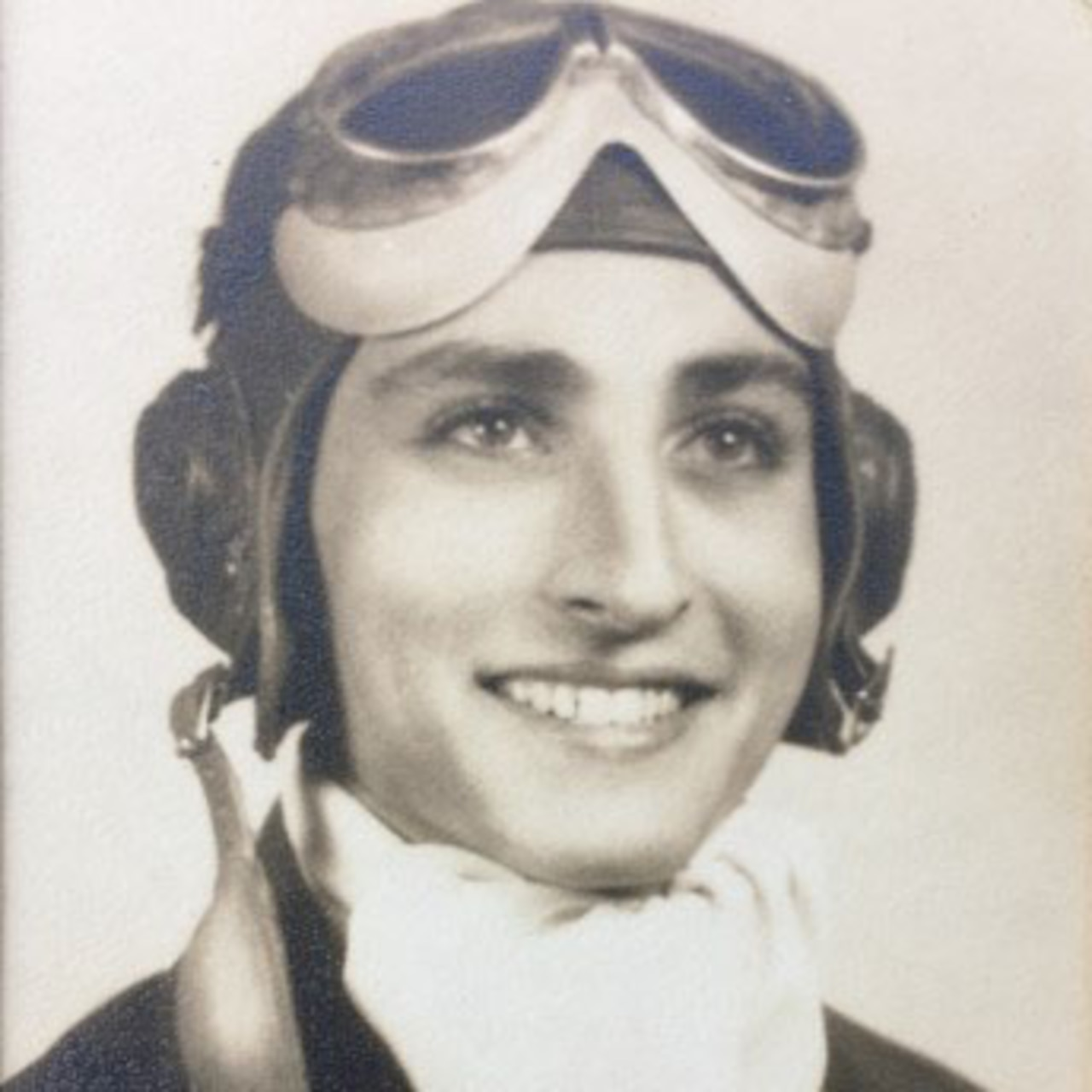 An old photo shows a young man with a broad smile dressed in an old-fashioned pilot's uniform and goggles.
