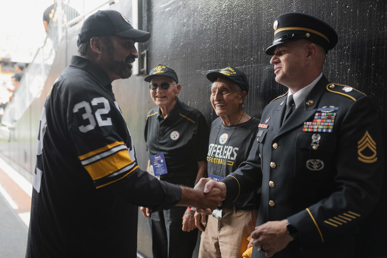 A former football player wearing a number 32 jersey shakes hands with a man in a military uniform as two elderly men look on.