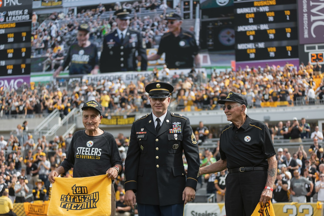 "Two elderly men stand on a football field holding yellow banners; they are wearing caps with the words ""World War II veteran."" In the background, the bleachers are filled with spectators; above the crowd, the men can be seen on a giant video screen. Between the elderly men stands in younger man wearing an Army uniform."