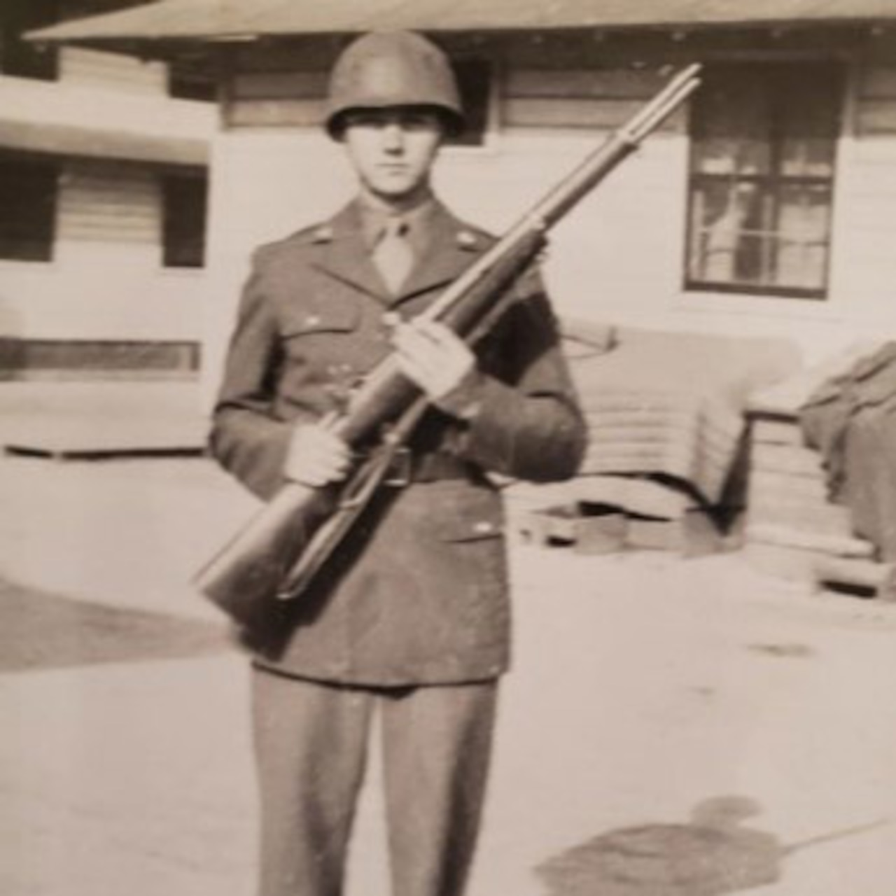A young man dressed in an Army uniform poses hold up his rifle for a photo.