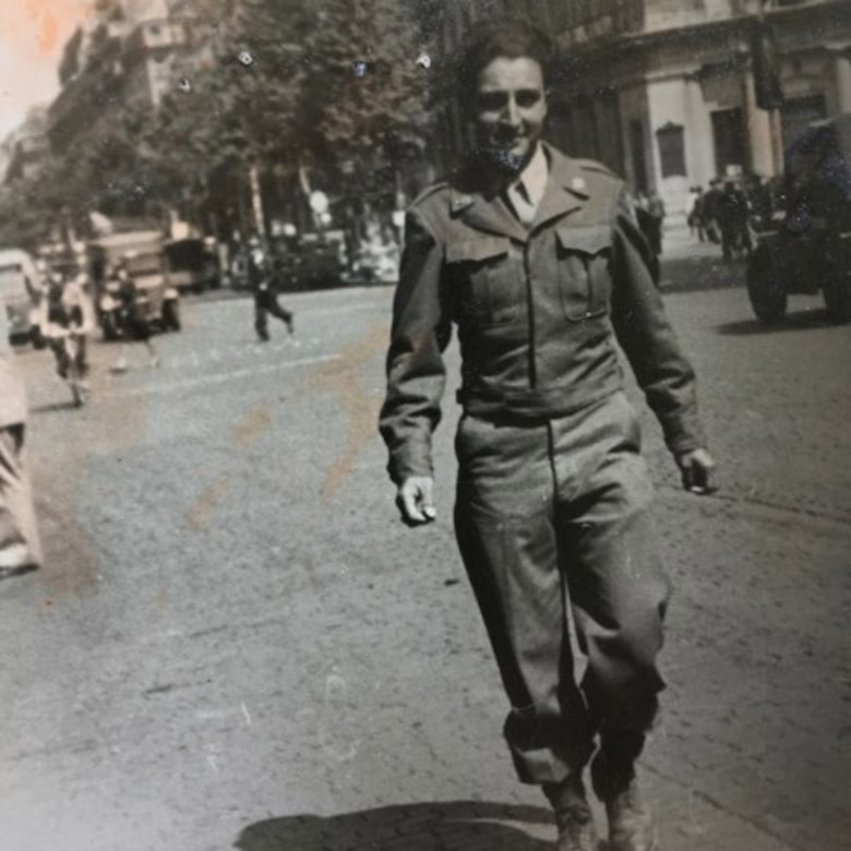 Historic photo of a manan in a U.S. Army uniform walking down a street.