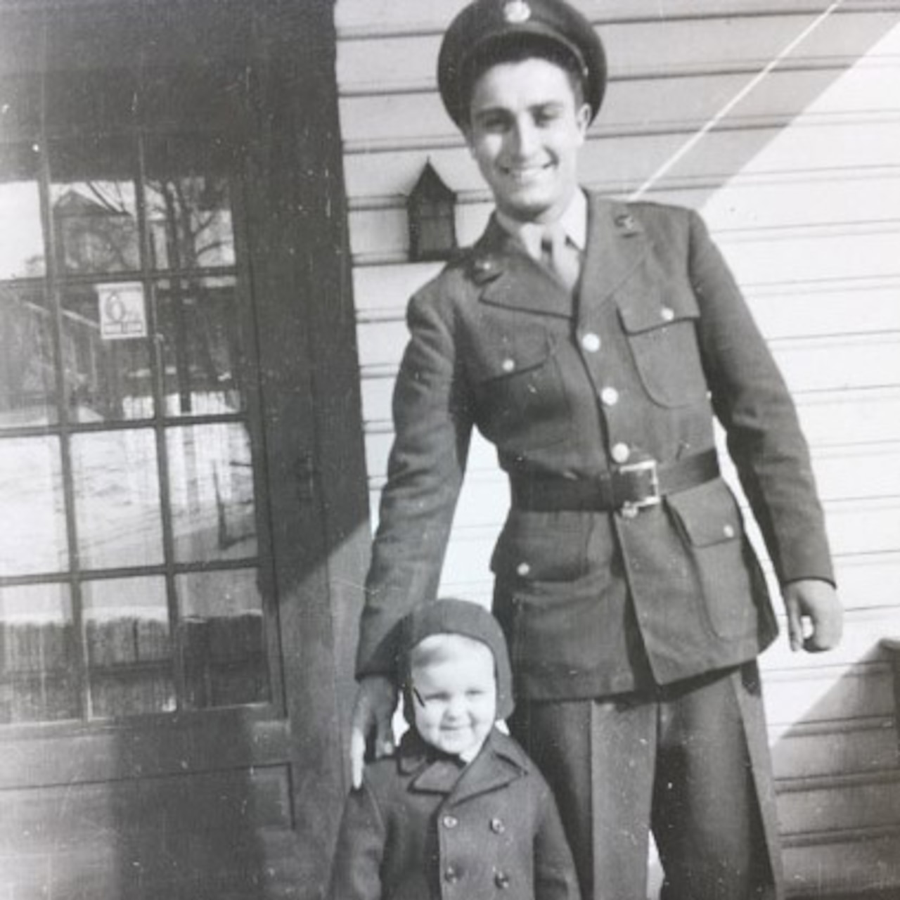 Man in an Army uniform smiles as he stands next to a small child, who is wearing a hat and coat
