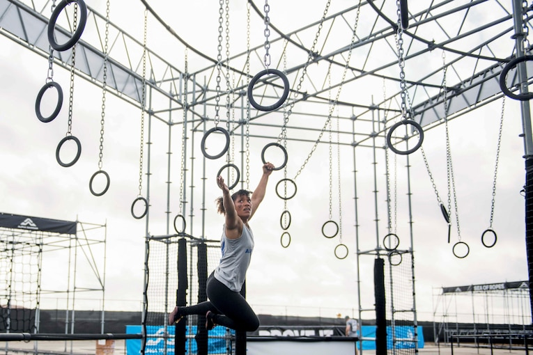 An airman swings on rings hanging from a metal structure.