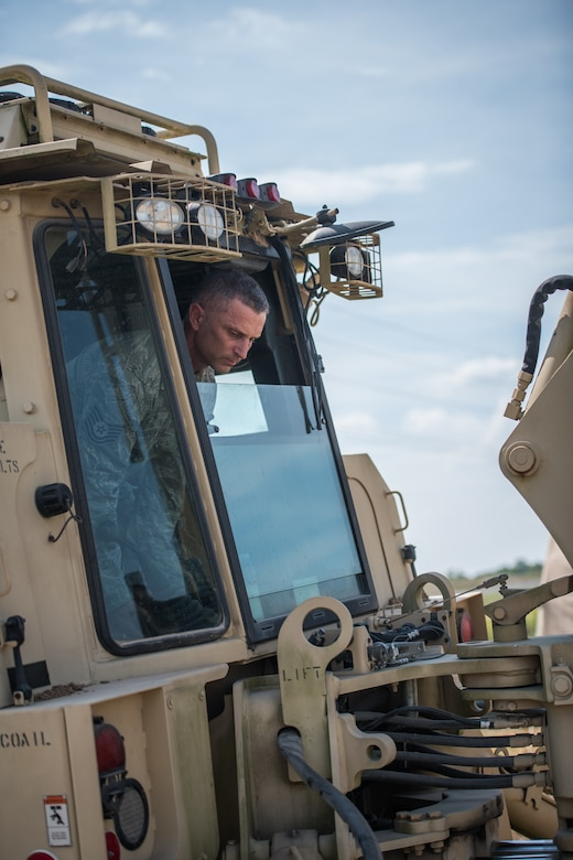 Tech. Sgt. Casey Goodaker,  932nd Civil Engineer Squadron technician, takes a closer look while positioning the backhoe bucket during field training, Sept. 10, 2019 at the Sparta National Guard training area, Sparta, Illinois. The 932nd CES spent two days at the training facility using the space for heavy equipment training, something they are not able to perform at Scott Air Force Base during unit training assemblies.  (U.S. Air Force photo by Master Sgt. Christopher Parr)
