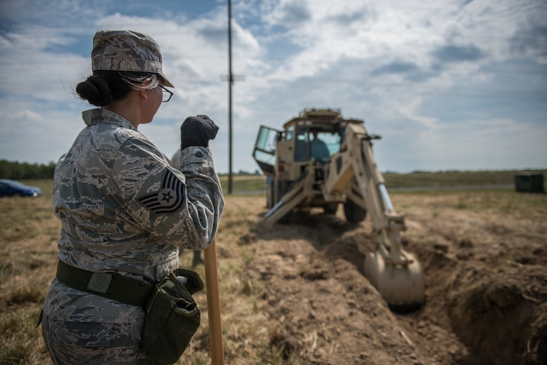 U.S. Air Force Reserve Citizen Airman Tech. Sgt. Tiana Corpuz looks on from a safe distance as Tech. Sgt. Casey Goodaker operates a backhoe to unearth a simulated water-main needing repairs during field training, Sept. 10, 2019 at the Sparta National Guard training area, Sparta, Illinois. The 932nd Civil Engineer Squadron spent two days at the training facility using the space for heavy equipment training, something they are not able to perform at Scott Air Force Base during unit training assemblies. (U.S. Air Force photo by Master Sgt. Christopher Parr)