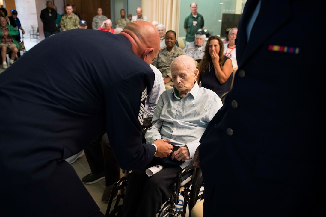 Chief Master Sgt. Christopher M. Yevchak, Air Force District of Washington command chief, left, presents the Armed Forces Retirement Home's oldest Airman, Humphrey Rourk, with a coin during the 72nd Air Force birthday event at the AFRH in Washington D.C., Sept. 13, 2019. (U.S. Air Force photo by Master Sgt. Michael B. Keller)