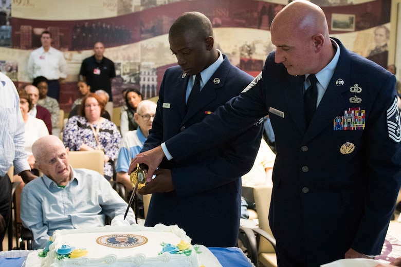 Chief Master Sgt. Christopher M. Yevchak, Air Force District of Washington command chief, Airman First Class Keyshawn Frazier, AFDW's youngest Airman, and Humphrey Rourk, the Armed Forces Retirement Home's oldest Airman, right to left, cut a cake during the 72nd Air Force birthday event at the AFRH in Washington D.C., Sept. 13, 2019. (U.S. Air Force photo by Master Sgt. Michael B. Keller)