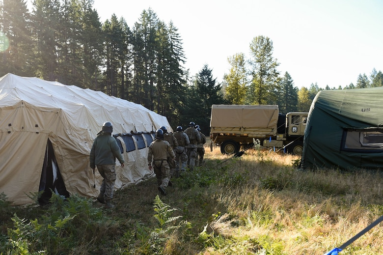 A team of five tactical air control party (TACP) officer candidates move towards a mock-deployment tactical village to complete a combat leadership objective challenge as part of TOPT selection course phase II on Joint Base Lewis-McChord, Wash., Aug. 27, 2019. TOPT is the selection process for officers who want to join the TACP career field in the U.S. Air Force.