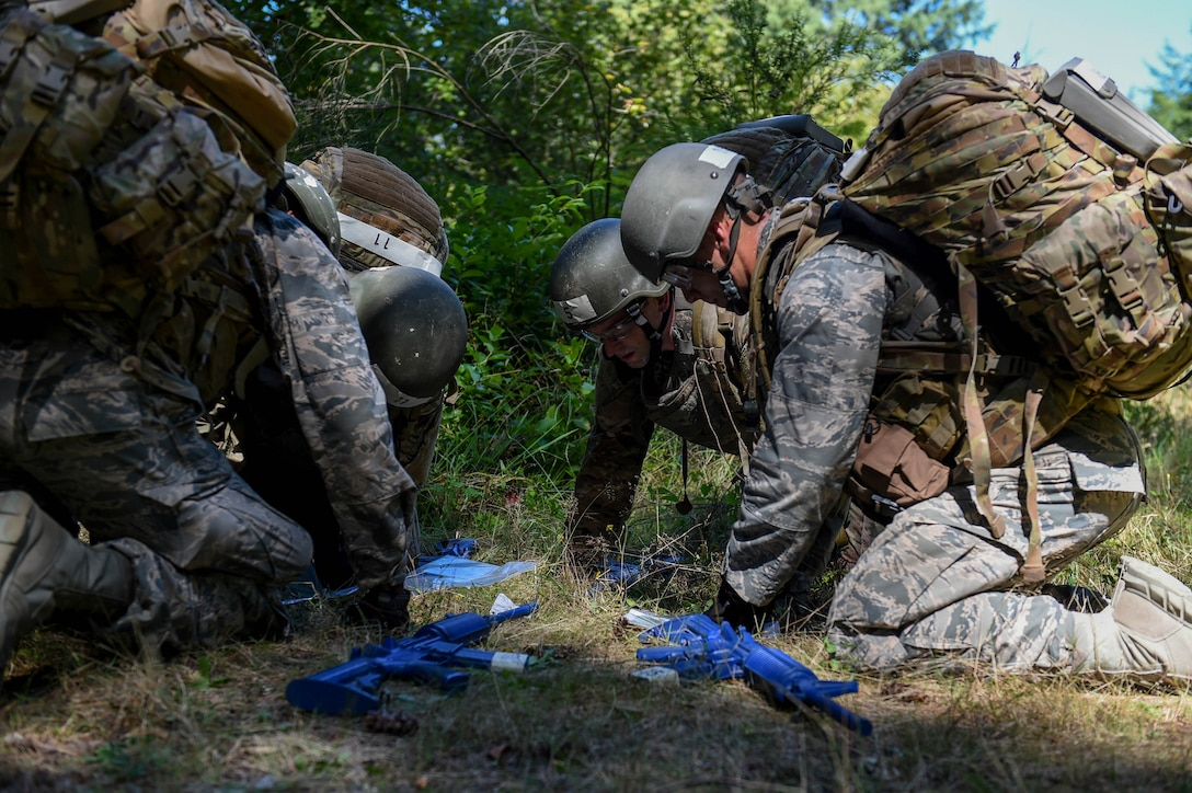 A team of tactical air control party (TACP) officer candidates examine a map of the area in preparation for a land navigation exercise on Joint Base Lewis-McChord, Wash., Aug. 27, 2019. Candidates were required to navigate to five different coordinates where a different team challenge awaited them at each new location.
