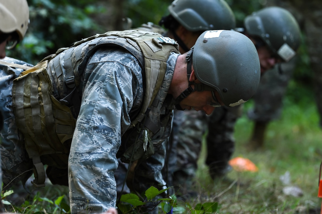 A team of tactical air control party (TACP) officer candidates, participating in a land navigation exercise during the TOPT selection course phase II, perform push-ups as an added element of stress while working on a team problem-solving activity Joint Base Lewis-McChord, Wash., Aug. 27, 2019. Candidates were evaluated on their performance under high levels of stress by experienced TACP officer and enlisted cadre, as well as Air Force psychologists throughout the week-long selection process.