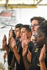 young men and women hold up their right hand to take an oath to enlist in the Army