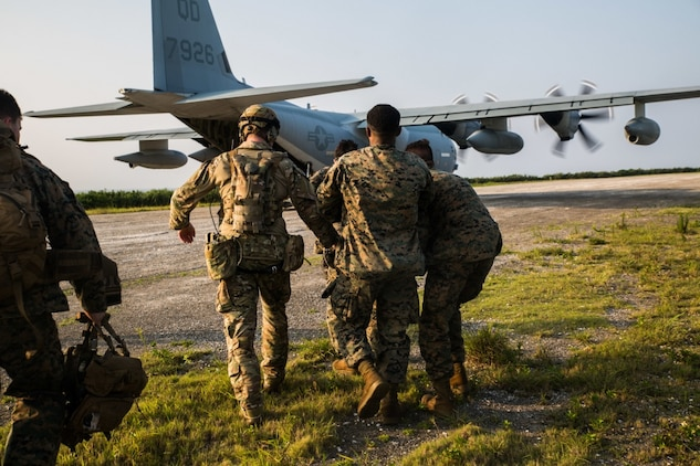 Marines with Echo Company, Battalion Landing Team, 2nd Battalion, 1st Marines, 31st Marine Expeditionary Unit, carry a simulated casualty to a KC-130 during a simulated airfield seizure after a long-range raid from the amphibious assault ship USS Wasp (LHD 1) at Ie Shima Training Facility, Okinawa, Japan, Aug. 13, 2019. The 31st MEU and Amphibious Squadron 11, aboard Wasp Amphibious Ready Group ships, conducted a series of sequential operations which simulated naval expeditionary combined-arms maneuver from amphibious assets to shore, utilizing Marine Air-Ground Task Force capabilities integrated across all warfighting domains. (U.S. Marine Corps photo by Lance Cpl. Kenny Nunez Bigay)