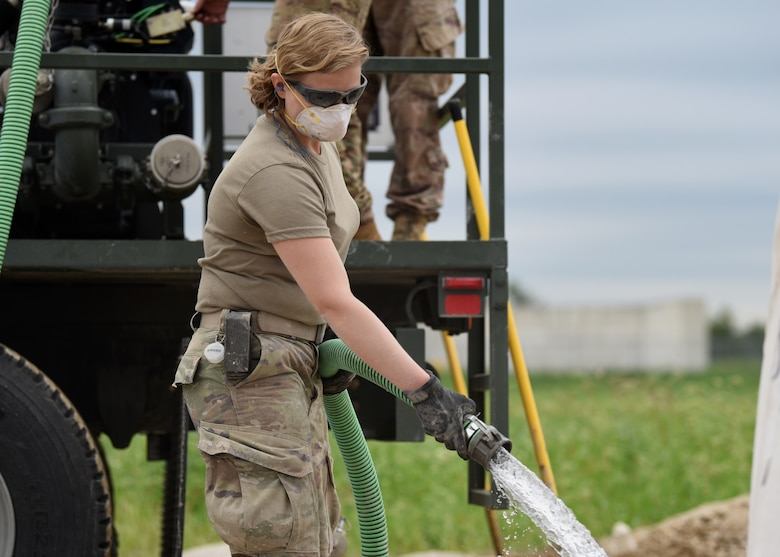 Senior Airman Madison Bowden-Parker, 51st Civil Engineer Squadron structural journeyman, fills a repair site with water and a specialized concrete mix during the 51st CES' biannual rapid airfield damage repair training on Osan Air Base, Republic of Korea, September 12, 2019. The training began on September 9 with members of different career fields across the 51st CES learning which piece of heavy equipment they would be operating in a real world scenario should the airfield be damaged. (U.S. Air Force photo by Senior Airman Denise M. Jenson)