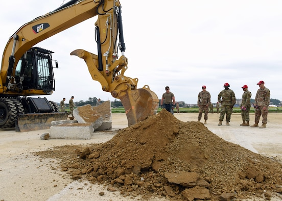 Airmen from the 51st Civil Engineer Squadron and the 554th Rapid Engineer Deployable Heavy Operational Repair Squadron assigned to Andersen Air Force Base, Guam, watch as an excavator rips up a section of concrete during the 51st CES' biannual rapid airfield damage repair training on Osan Air Base, Republic of Korea, September 12, 2019. This training is designed to demonstrate the squadron's ability to rapidly repair the airfield after its been damaged. (U.S. Air Force photo by Senior Airman Denise Jenson)
