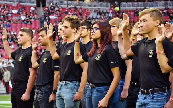 group of young men and women hold up their right hands as part of taking the oath of enlistment.