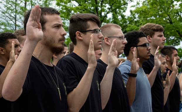 a group of young men and women hold up their right hands to enlist in the United States Army.