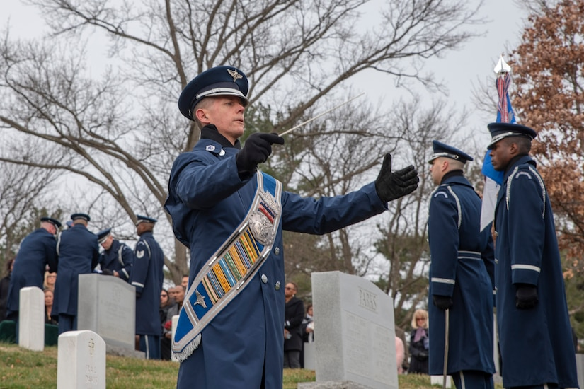 An airman in a dress uniform and winter coat holds his hands up to conduct a band. Two men stand in formation facing him. Several mourners are in the background near gravestones.