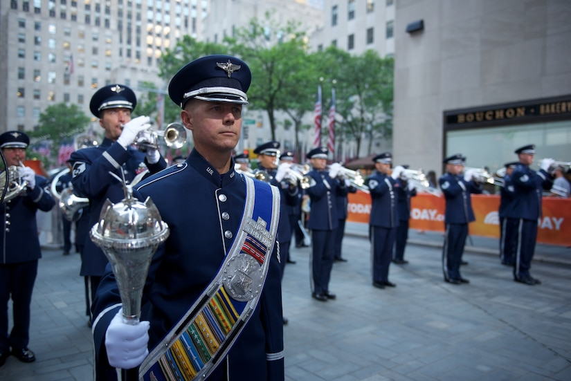 An airman wearing a formal hat, sash and mace stands in the foreground while several other airmen play brass instruments  in the background. Two U.S. flags are in the background.