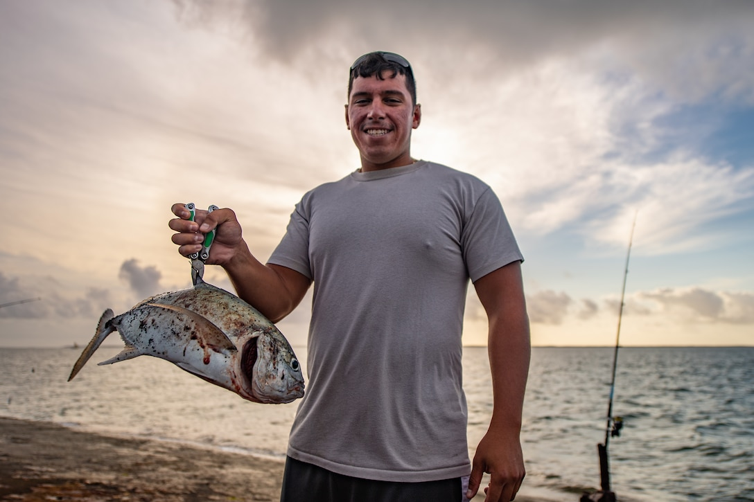 U.S. Air Force Tech. Sgt. Gary Yates, 475th Expeditionary Air Base Squadron air operations noncommissioned officer in charge, poses with a fish he caught at a pier near Camp Simba, Kenya, Aug. 29, 2019. Yates is responsible for managing incoming and outgoing cargo and passengers between Camp Simba and other military installations within the area of responsibility. During his time in Kenya, Yates often wakes up hours before work to go fishing at the pier with his friends. (U.S. Air Force photo by Staff Sgt. Devin Boyer)