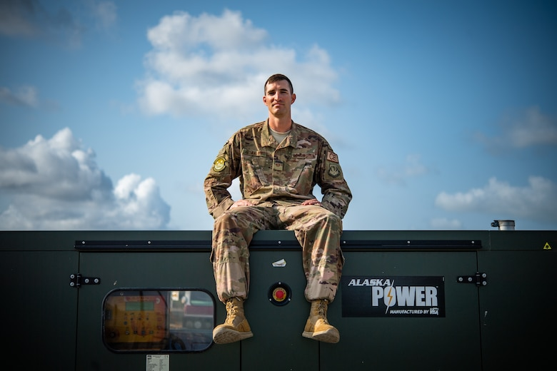 U.S. Air Force Tech. Sgt. Alexander Stanley, 475th Expeditionary Air Base Squadron electrical systems noncommissioned officer in charge, poses for a photo on top of a generator at Camp Simba, Kenya, Sep. 2, 2019. Stanley, originally from Vancouver, Washington, is responsible for quality assurance on electrical construction projects and the maintenance for the 3,000 ft runway lighting system at Camp Simba. At home he enjoys building and working on cars. During his deployment, he enjoys working on construction projects to improve quality of life around the compound. (U.S. Air Force photo by Staff Sgt. Devin Boyer)