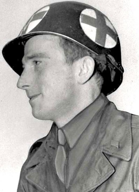 A man wearing a medic's helmet looks left.