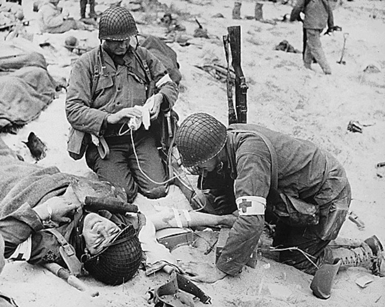 Combat medics wearing the Red Cross armbands put an IV into the arm of a soldier on the battlefield in France during World War II.