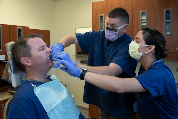 U.S. Air Force Col. Jeffrey Nelson, left, 60th Air Mobility Wing commander, undergoes a dental procedure done by Chief Master Sgt. Derek Crowder, 60th AMW command chief, and Senior Airman Rosemarie Rivera, 60th Dental Squadron dental assistant, as part of Leadership Rounds Sept. 13, 2019, at David Grant USAF Medical Center, Travis Air Force Base, California. The Leadership Rounds program involves wing leadership interacting with Airmen to get a detailed view of each mission performed at Travis AFB. (U.S. Air Force photo by Heide Couch)