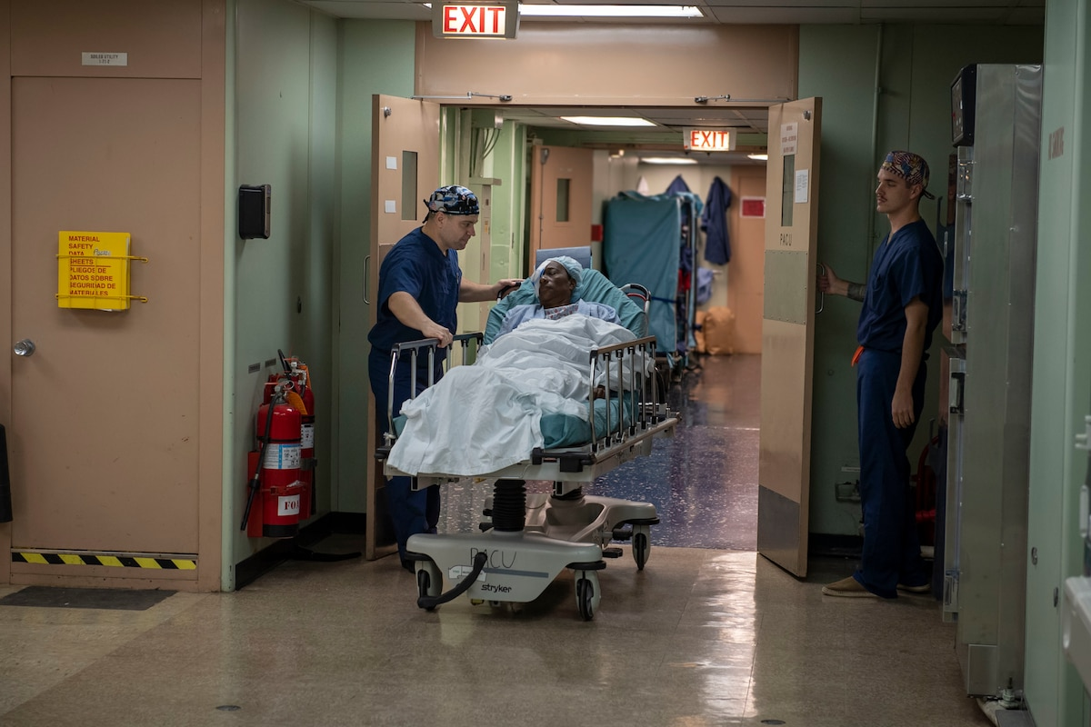 Surgical staff transports a woman into a post-anesthesia care unit.