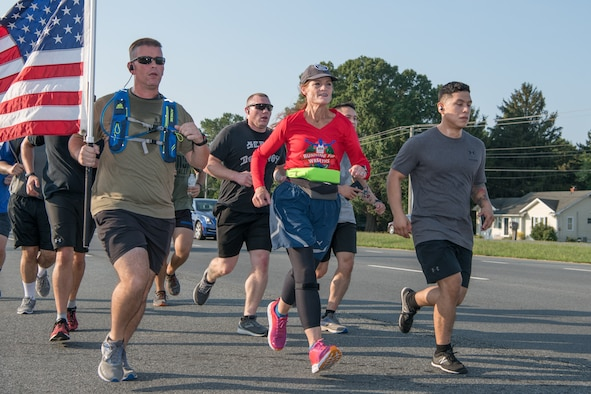 "Master Sgt. Trevor Derr, 736th Aircraft Maintenance Squadron C-17 production superintendent (with flag), and Cathy Powers, Gold Star Mother, run alongside members of Team Dover during the ""Running Fir Wreaths"" campaign Sept. 12, 2019, outside Dover Air Force Base, Del. Powers plans to run 1,000 miles across all 50 states in honor of her son and fallen veterans. (U.S. Air Force Photo by Mauricio Campino)"