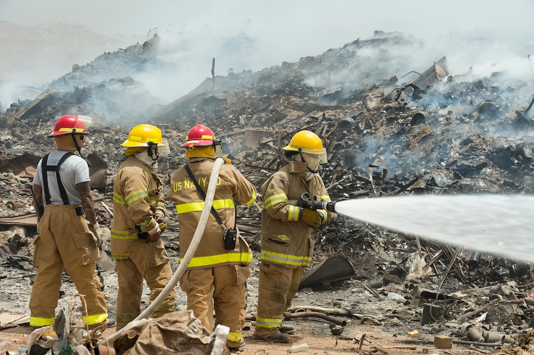 Firefighters use a hose to spray water on a fire at a landfill.