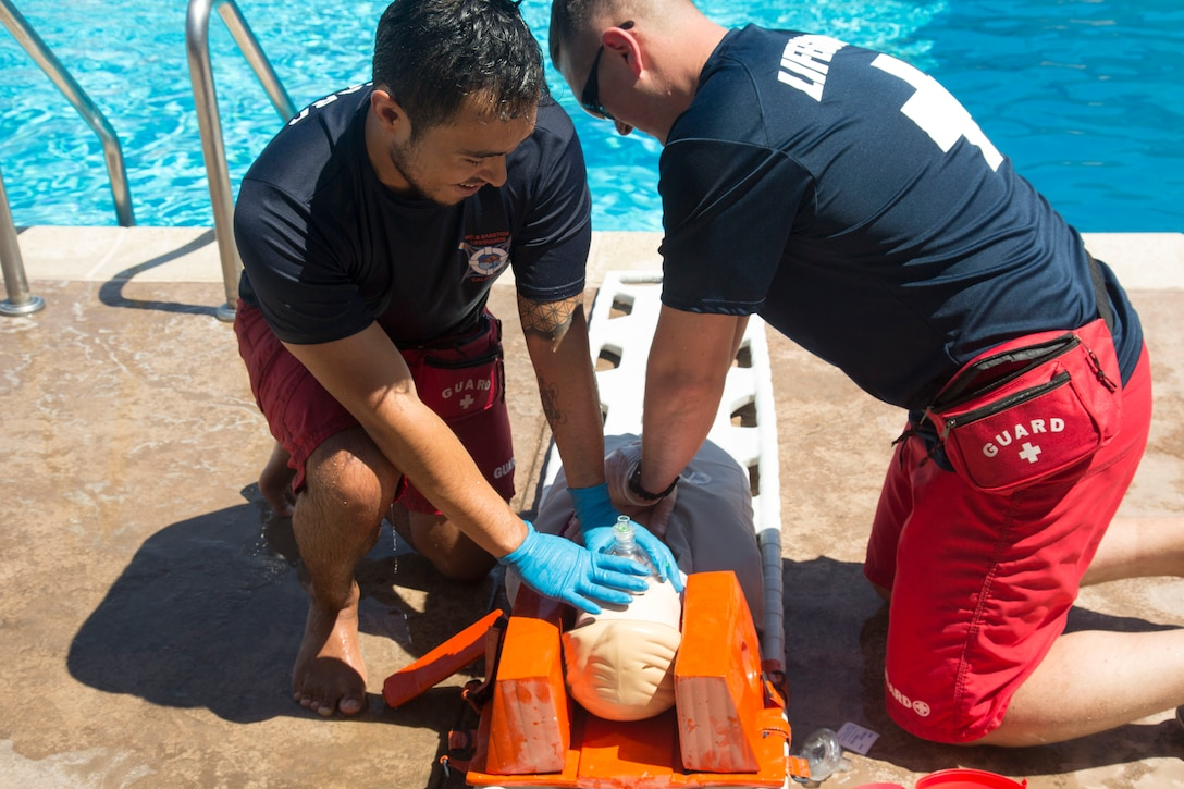 Francisco Cadillo, primary lifeguard, has delivered two breaths to a breath tube apparatus to the mouth of the drowning victim, in this case a resuscitation training manikin, as Sgt. Maxim Krymov, volunteer Marine lifeguard, delivers 30 chest compressions to the victim during an Emergency Action Plan training exercise in conjunction with rescue elements of the Marine Corps Fire Department. The two breaths and 30 - compression cycle continues until the victim is revived or fire department personnel arrive to take over the rescue effort.