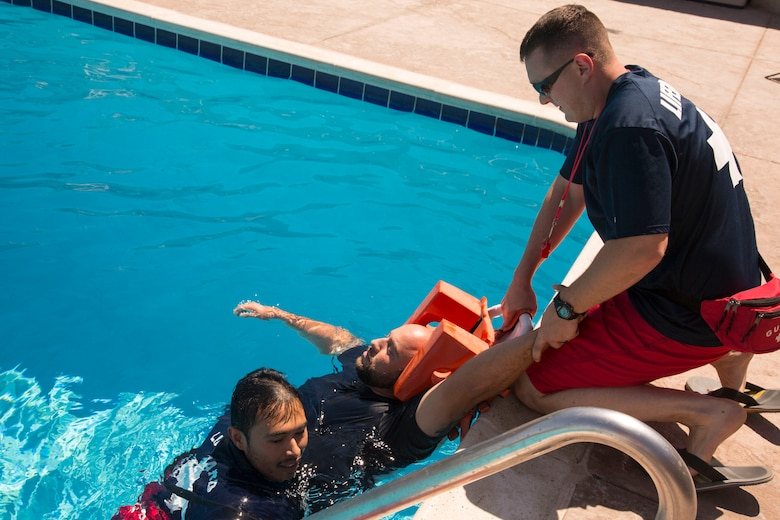 """Primary lifeguard Francisco Cadillo ensures drowning """"victim"""" Axel Rivera, lifeguard supervisor, is in place on the rescue backboard and one of Rivera's arms is held firmly by Sgt. Maxim Krymov, volunteer Marine lifeguard, while Cadillo gets out of the pool to help Krymov pull the backboard up on to the pool deck. The Oasis Pool lifeguards and rescue elements of the Marine Corps Fire Department participated in the Emergency Action Plan training exercise August 27."""