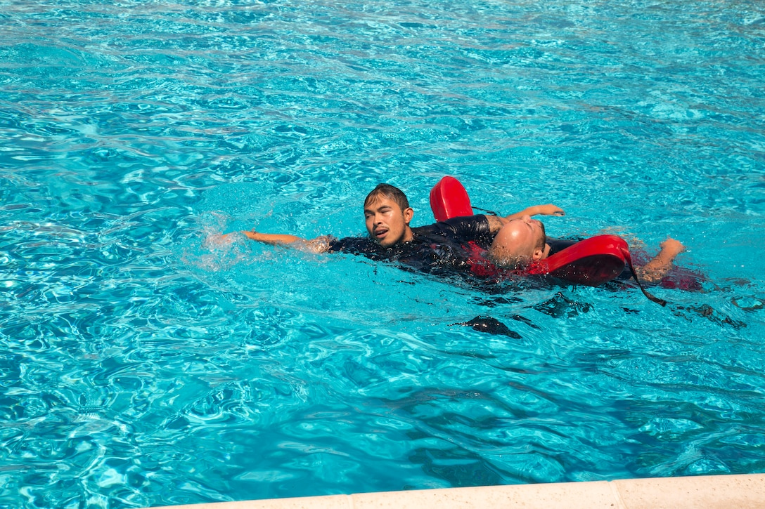 "Francisco Cadillo, primary lifeguard, Oasis Pool, has just recovered passive and unresponsive drowning ""victim"" Axel Rivera, lifeguard supervisor, from the bottom of the pool during an Emergency Action Plan training exercise August 27. Elements of the Marine Corps Fire Department also participated in this first ever special training exercise to ensure the Oasis Pool and fire department personnel remain trained and ready to go at a moment's notice to keep the MCLB Barstow aquatics center a safe place for pool patrons."