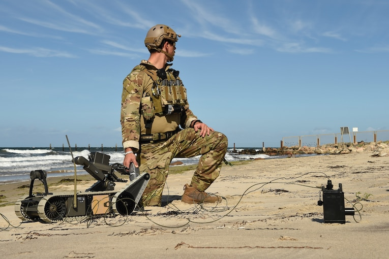 A man kneels on a beach with a small robotic device next to him.