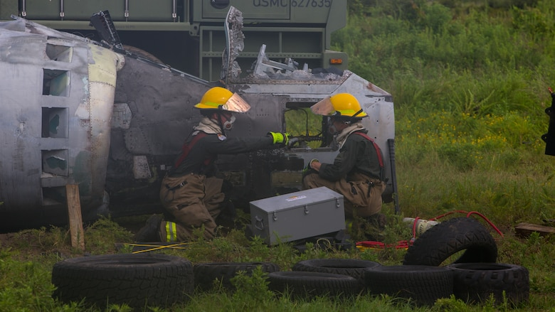 Aircraft Recovery and Fire Fighting (ARFF) Marines assess damage of a crashed plane during an aircraft recovery scenario at Marine Corps Auxiliary Landing Field Bogue, North Carolina, Aug. 16, 2019. ARFF Marines attached to Marine Wing Support Detachment 273 trained to improve readiness, efficiency, and recovery times.