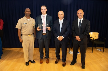 Michael Peduto, Contracts Division head, receives the Rear Adm. Grace Hopper Award the Naval Surface Warfare Center, Carderock Division Honor Awards on Sept. 10, 2019, in West Bethesda, Md. With Peduto is Commanding Officer Capt. Cedric McNeal, Technical Director Larry Tarasek and Contracting and Acquisition Department Head Tariq Al-Agba. (U.S. Navy photo by Nicholas Brezzell/Released)