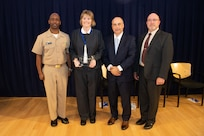 Dr. Maureen Foley, Composites Team lead, receives the Rear Adm. Benjamin Isherwood Award the Naval Surface Warfare Center, Carderock Division Honor Awards on Sept. 10, 2019, in West Bethesda, Md. With Foley is Commanding Officer Capt. Cedric McNeal, Technical Director Larry Tarasek and Platform Integrity Department Head Jeff Mercier. (U.S. Navy photo by Nicholas Brezzell/Released)