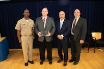 Paul Young, program and engineering manager for Columbia and Virginia pressure hull model programs, receives the Rear Adm. George Melville Award the Naval Surface Warfare Center, Carderock Division Honor Awards on Sept. 10, 2019, in West Bethesda, Md. With Young is Commanding Officer Capt. Cedric McNeal, Technical Director Larry Tarasek and Platform Integrity Department Head Jeff Mercier. (U.S. Navy photo by Nicholas Brezzell/Released)