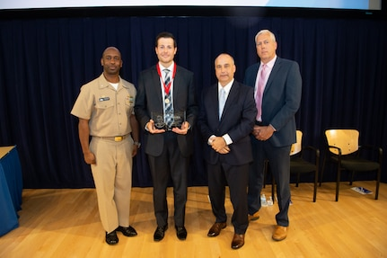 Bradley Schafer, head of the Columbia-class Submarine Management Branch, receives the Capt. Harold Saunders Award the Naval Surface Warfare Center, Carderock Division Honor Awards on Sept. 10, 2019, in West Bethesda, Md. With Schafer is Commanding Officer Capt. Cedric McNeal, Technical Director Larry Tarasek and Naval Architecture and Engineering Department Head Mike Brown. (U.S. Navy photo by Nicholas Brezzell/Released)