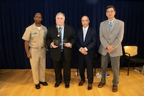 Dr. John Holmes, senior scientific technical manager for underwater electromagnetics, receives the inaugural Dr. Murray Strasberg Award the Naval Surface Warfare Center, Carderock Division Honor Awards on Sept. 10, 2019, in West Bethesda, Md. With Holmes is Commanding Officer Capt. Cedric McNeal, Technical Director Larry Tarasek and Ship Signatures Department Head Dr. Paul Shang. (U.S. Navy photo by Nicholas Brezzell/Released)