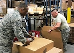 Air Force Master Sgt. Brian Swayne and Army Capt. Garland Fleming II, both DLA Land and Maritime reservists, pack and mark bare items as part of an effort to reduce suspended stock at DLA Distribution warehouses. Courtesy photo