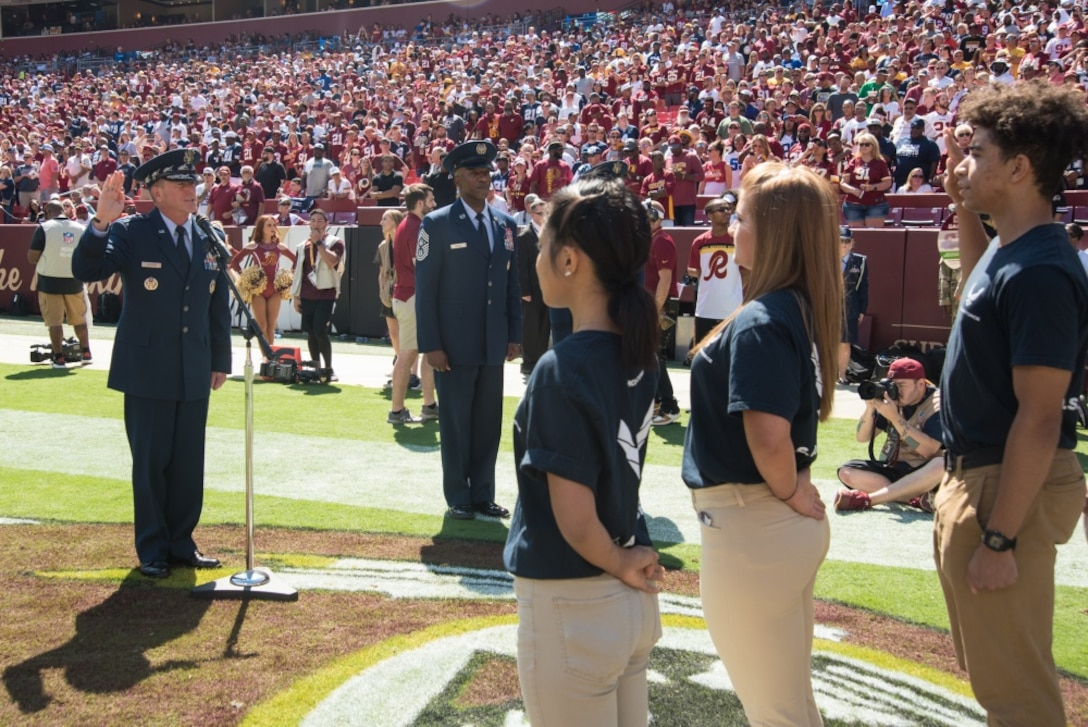 A referee reviews the coin toss at the Washington Redskins vs. Dallas Cowboys game at FedEx Field, September 15, 2019. Air Force Chief of Staff Gen. David L. Goldfein presented his coin for the opening ceremony in honor of the Air Forces 72nd birthday. (U.S. Air National Guard photo by Tech. Sgt. Erica Flores)
