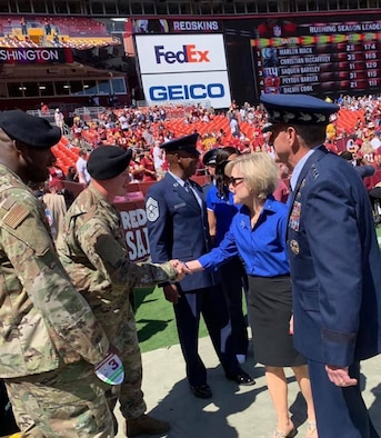 Tech. Sgt. Eugene Harrison, non-commissioned officer in charge of combat arms, and Staff Sgt. Alan Muhle, military working dog handler, shake hands with Dawn Goldfein, spouse to Air Force Chief of Staff Gen. Dave Goldfein during the NFL Washington Redskins vs. Dallas Cowboys matchup at FedEx Field in Landover, Maryland, Sept. 15.