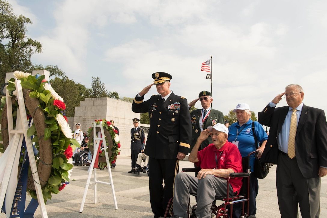 A veteran in a wheelchair and four other people salute a wreath.