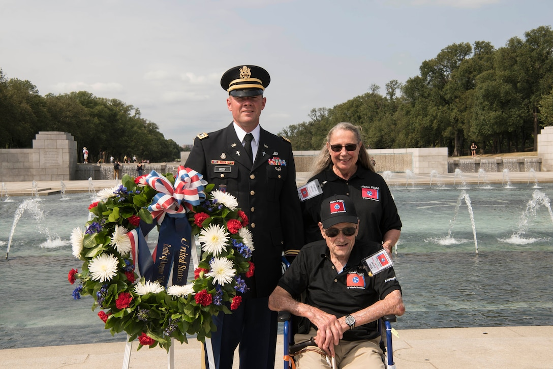 A man in a wheelchair, a man in a military uniform and a woman stand next to a wreath at the World War II Memorial.