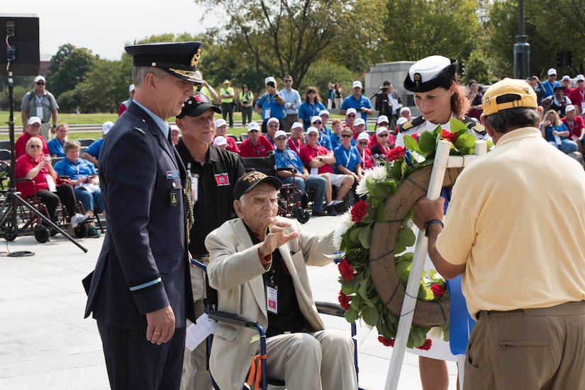 A man in a wheelchair helps place a wreath at an outdoor event.  He is accompanied by two military personnel and a man behind him pushing his chair.