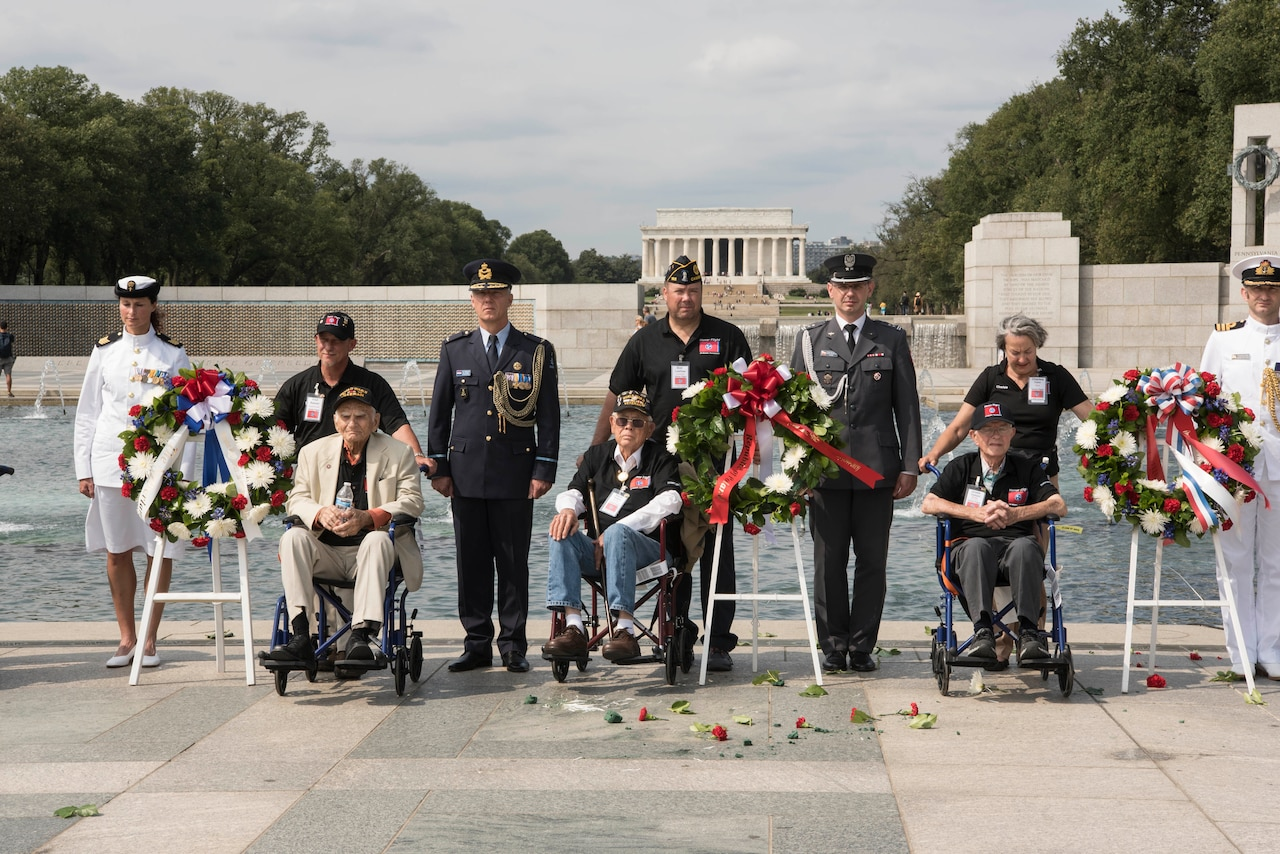Three men in wheelchairs sit next to wreaths at an outdoor location. They are accompanied by both men and women in military uniforms. In the background are portions of the World War II Memorial and the Lincoln Memorial.
